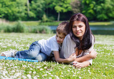 Mother and son lying on grass. Mother and son lying on the grass in a park in bright sunny day Royalty Free Stock Photos