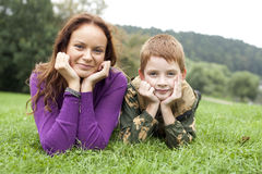 Mother and son lying on the green grass stock images
