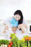 Mother and son make salad for lunch. Happy young mother and her son make vegetables salad for lunch in the kitchen at home Royalty Free Stock Photos