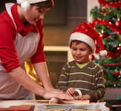 Mother and son making christmas cake. Son watching mum's hand, smiling Stock Image