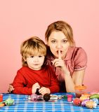 Mother and son making Easter decorations. Woman and child with happy faces on pink background. Mom and boy spend time. Together showing silence sign. Easter royalty free stock photography