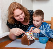 Mother and son making gingerbread house Royalty Free Stock Photos