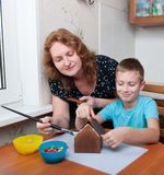 Mother and son making gingerbread house Stock Images