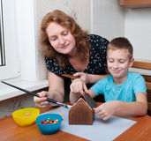 Mother and son making gingerbread house Stock Photography