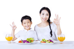 Mother and son love healthy salad - isolated. Mother and son making OK gesture while having salad, isolated on white Royalty Free Stock Photography