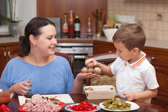 Mother and son making pizza together. At home royalty free stock photography