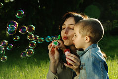 Mother and son making soap bubbles Stock Photos