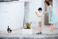 Mother and son met a cat while walking narrow streets ot typical italian town. Young mother and her son met a cat while walking narrow streets ot typical italian Stock Photos