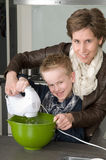 Mother and son mixing the dough. Mother and son are mixing the dough for the cake Royalty Free Stock Photography