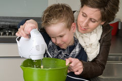 Mother and son mixing the dough. Mother and son are mixing the dough for the cake Royalty Free Stock Photos