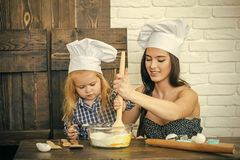 Mother and son mixing flour and eggs in bowl. Woman and child boy in chef hats with spoon. Happy family in kitchen. Homemade baking and cooking. Mothers day stock photos