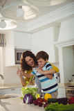 Mother and son mixing the salad in kitchen Stock Images