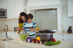 Mother and son mixing the salad in kitchen Stock Photos