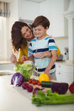 Mother and son mixing the salad in kitchen Stock Image