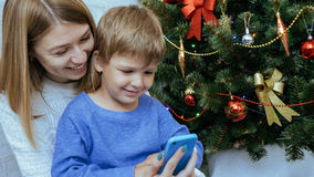 Mother and son with mobile phone are sitting together near christmas tree. Young happy mother and son with mobile phone are sitting together near decorated Stock Photos