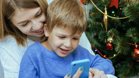 Mother and son with mobile phone are sitting together near christmas tree. Young happy mother and son with mobile phone are sitting together near decorated Royalty Free Stock Photos