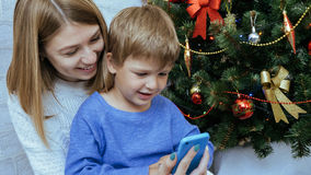 Mother and son with mobile phone are sitting together near christmas tree. Young happy mother and son with mobile phone are sitting together near decorated Stock Photography