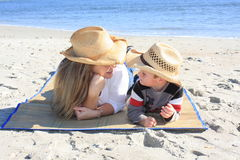 Mother and son moment. A young woman anda small boy laying on the beach, looking at each other royalty free stock photography