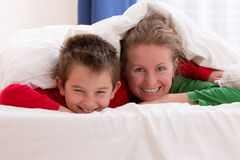 Mother and Son Moments. Mother and her son under the blanket with Christmas color pajamas, smiling to you while having great moments Royalty Free Stock Photography