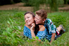 Mother and son in nature. Mother and son lie on the grass outdoors in summer Stock Photo