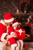 Mother and son near Christmas fireplace Stock Photo