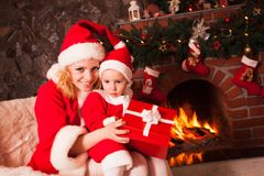 Mother and son near Christmas fireplace Stock Images