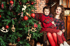 Mother and son near a Christmas tree. Family celebration of the New Year. Mother and sonnear a Christmas tree. Giving gifts. Holiday and fun royalty free stock photo