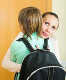 Mother and son near door. Positive mature mother hugging and lecturing boy before he goes to school stock image