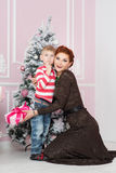 Mother with son near fir tree with gift. Christmas, New Year Royalty Free Stock Images