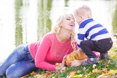 Mother and son near lake with pumpkin, autumn time. Young pretty mother and son with pumpkin near lake, autumn time Royalty Free Stock Image