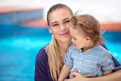 Mother with son near pool. Portrait of charming mother with cute little son sitting near poole and enjoying warm sunny day, spending summer holidays on the beach stock image