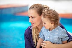 Mother with son near pool. Portrait of charming mother with cute little son sitting near pool, spending summer holidays on the beach resort stock photography