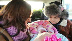 Mother, son and newborn baby ride in the car. stock footage