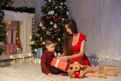 Mother and son open Gifts Christmas lights new year gifts stock image