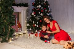 Mother and son open up gifts from Christmas New Year holiday house stock image