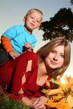 Mother and son outdoors. Young beautiful mother lying on green grass with her son and holding bouquet of yellow autumn leaves Stock Photo