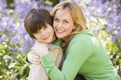 Mother and son outdoors embracing and smiling Stock Images