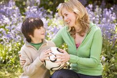 Mother and son outdoors holding ball smiling Royalty Free Stock Photography