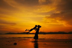A mother and son in outdoors at sunset with copy space. A mother and son playing on the beach and sea outdoors at sunset in happy holiday vacation time with copy stock photo