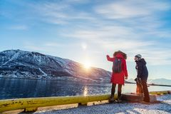 Mother and son outdoors on winter. Beautiful family of mother and son enjoying winter day outdoors in Tromso town surrounded by fjords in Northern Norway stock images