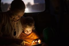 Mother and son with pad during car travel at night Stock Photo