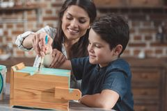 Young mother helping little son to paint a. Wooden birdhouse stock photos