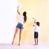 Mother and son paiting walls. In a new house stock photography