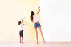 Mother and son paiting walls in a new house. Young mother and son paiting walls in a new house Stock Images