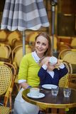 Mother in son in a Parisian cafe. Happy family of two spending fun together in an outdoor Parisian cafe, little boy is drinking his beverage Royalty Free Stock Images