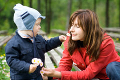 Mother and Son in the park. Spring day in the park. Mother smells flower which little son holds Stock Photo