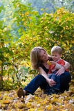 Mother and son in park. Plays with maple leaves Stock Image