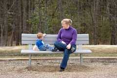 Mother and Son on park bench. Mother and son sitting on a park bench Stock Photo