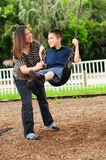 Mother and son at park on swing Stock Image