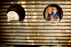 Mother and son peeks through hole at playground Royalty Free Stock Image